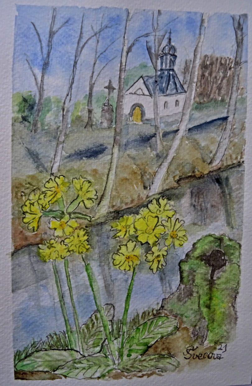 Kvetou petrklíče na břehu říčky, vzadu kaplička